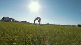 De jonge vrouwelijke turner voert gymnastiek- brug op het gras in zonnige dag uit stock footage