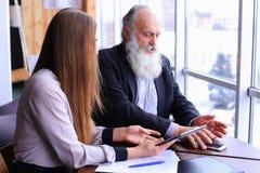 De jonge vrouwelijke werkgever debatteert de oude werknemer problemen in zaken bespreekt Royalty-vrije Stock Foto's