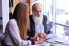 De jonge vrouwelijke werkgever debatteert de oude werknemer problemen in zaken bespreekt Stock Fotografie