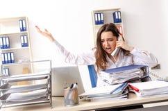 De jonge vrouwelijke werknemer ongelukkig met het bovenmatige werk royalty-vrije stock afbeelding