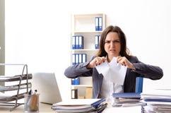 De jonge vrouwelijke werknemer ongelukkig met het bovenmatige werk stock foto's