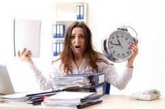De jonge vrouwelijke werknemer ongelukkig met het bovenmatige werk stock foto