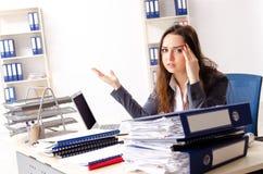De jonge vrouwelijke werknemer ongelukkig met het bovenmatige werk royalty-vrije stock fotografie