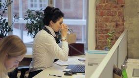 De jonge vrouwelijke werknemer roept partner op de telefoon in de grote open plek stock videobeelden