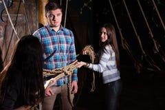 De jonge vrouwen binden een jonge kerel aan een kolom op het dek van een schip royalty-vrije stock afbeelding