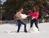 De jonge vrouwen bouwen sneeuwman Royalty-vrije Stock Afbeelding