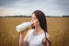 De jonge vrouwen drinkt erotically melk op een gebied Royalty-vrije Stock Foto's