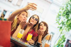De jonge vrouwen in een koffie na het winkelen maken selfie foto royalty-vrije stock afbeelding