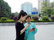 De jonge vrouwen en de oudere vrouwen gebruiken mobiele telefoons en WeChat stock afbeeldingen