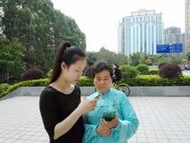 De jonge vrouwen en de oudere vrouwen gebruiken mobiele telefoons en WeChat royalty-vrije stock afbeeldingen