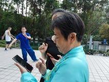 De jonge vrouwen en de oudere vrouwen gebruiken mobiele telefoons en WeChat royalty-vrije stock foto's