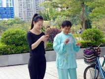 De jonge vrouwen en de oudere vrouwen gebruiken mobiele telefoons en WeChat royalty-vrije stock foto
