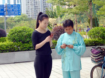 De jonge vrouwen en de oudere vrouwen gebruiken mobiele telefoons en WeChat royalty-vrije stock fotografie