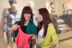 De jonge vrouwen met het winkelen doet het kopen kleren in kledingsopslag in zakken Stock Foto's