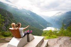 De jonge vrouwen ontspannen op Geiranger-fjord De gelukkige vrienden genieten van mooi meer en goed weer in Noorwegen Stock Fotografie
