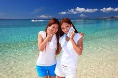De jonge vrouwen op het strand genieten van zonlicht Royalty-vrije Stock Foto's