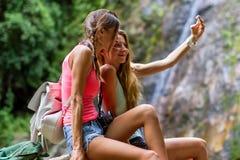 De jonge vrouwen rusten op de rotsen in de wilderniswaterval op de achtergrond Royalty-vrije Stock Afbeeldingen