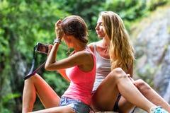 De jonge vrouwen rusten op de rotsen in de wilderniswaterval op de achtergrond Stock Foto's
