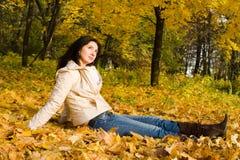De jonge vrouwen rusten op het de herfstblad Stock Foto
