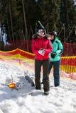 De jonge vrouwen in ski passen status dichtbij de omheining in een ski-toevlucht aan stock foto