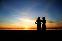 De jonge vrouwen van het silhouet op het strand Royalty-vrije Stock Afbeelding