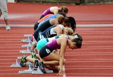 De jonge vrouwen volgen atleten in startblok bij de beginnende lijn Stock Foto