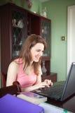 De jonge vrouwen werkt in een huisbureau Royalty-vrije Stock Afbeeldingen
