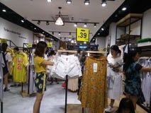 De jonge vrouwen winkelen voor kleren tijdens de nacht bij de kledingsopslag Stock Foto