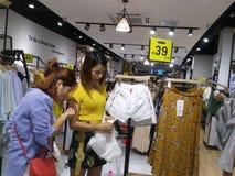 De jonge vrouwen winkelen voor kleren tijdens de nacht bij de kledingsopslag Stock Afbeelding