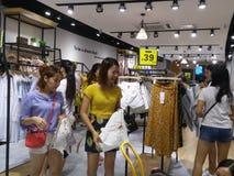 De jonge vrouwen winkelen voor kleren tijdens de nacht bij de kledingsopslag Stock Fotografie