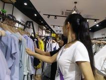 De jonge vrouwen winkelen voor kleren tijdens de nacht bij de kledingsopslag Stock Afbeeldingen