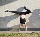 De jonge vrouwenacrobaat op handstand voert streng in openlucht tegen de muur uit royalty-vrije stock fotografie