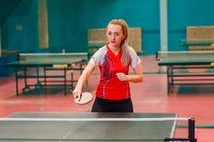 De jonge vrouwenatleet speelt pingpong royalty-vrije stock afbeelding