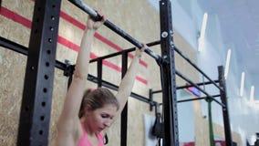 De jonge vrouwenatleet voert opwarming en trekkracht-UPS op de bar uit Mooi en atletisch meisje die aan zich werken stock video