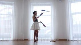 De jonge vrouwenballerina voert circus het jongleren met uit zich bevindt dichtbij het venster stock footage