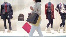 De jonge vrouwengangen langs een showvenster met zakken en telefoon in haar dienen het winkelcomplex in Het zijaanzicht dolly sch stock video