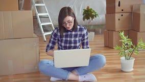 De jonge vrouwengedachte op de achtergrond van te bewegen reparaties of dozen zich stock videobeelden
