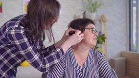 De jonge vrouwenhulp zet een gehoorapparaat op het oor van hard van hoorzittingsvrouw stock videobeelden