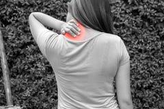 De jonge vrouwennek of de gezamenlijke pijn bij openlucht in zwart-wit bedriegt Royalty-vrije Stock Foto