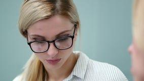 De jonge vrouwenpsycholoog in glazen spreekt emotioneel met haar cliënt stock videobeelden