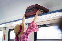 De jonge vrouwenreiziger in hoed zet de koffer op de hoogste plank in de trein Royalty-vrije Stock Afbeeldingen
