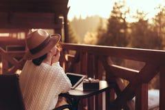 De jonge vrouwenreiziger zit bij het terras met een tablet stock foto
