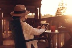 De jonge vrouwenreiziger zit bij het terras met een tablet stock fotografie