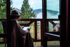 De jonge vrouwenreiziger zit bij het terras met een tablet tegen mooi berglandschap tijdens reis stock afbeelding