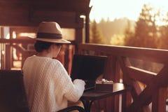 De jonge vrouwenreiziger zit bij het terras met laptop stock afbeelding