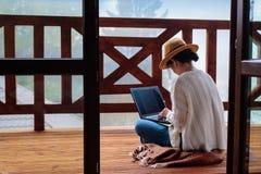 De jonge vrouwenreiziger zit bij het terras met laptop tegen mooi berglandschap tijdens reis royalty-vrije stock afbeeldingen