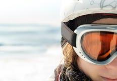 De jonge vrouwenskiër bij de toevlucht van de de winterski in bergen, ziet dicht omhoog onder ogen Stock Foto