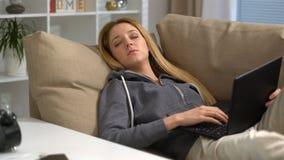 De jonge vrouwenslaap met laptop op de bank thuis, ontwaakt plotseling en gaat opnieuw naar slaap stock videobeelden