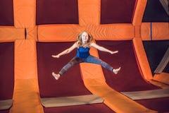 De jonge vrouwensportman die op een trampoline in geschiktheid springen parkeert royalty-vrije stock foto