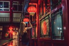 De jonge vrouwentoerist bekijkt de Chinese traditionele lantaarns Chinees Nieuwjaar Reis naar het concept van China royalty-vrije stock afbeeldingen